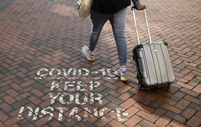 A person wheeling a suitcase passes a message painted on the floor, reminding people to social distance due to COVID-19