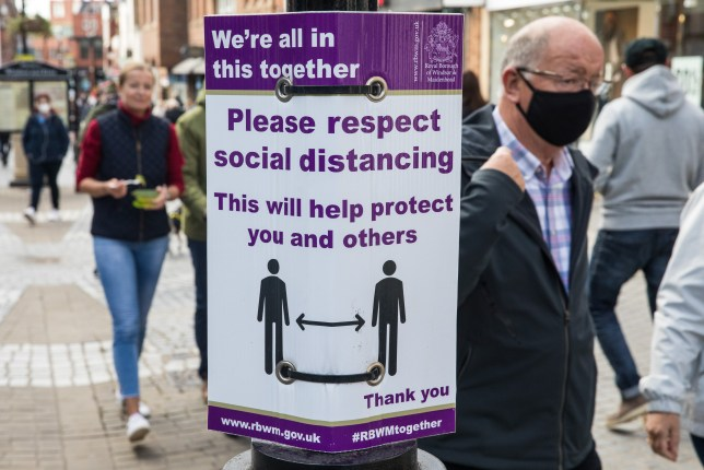 A man wearing a face covering walks past a sign reminding people to social distance.