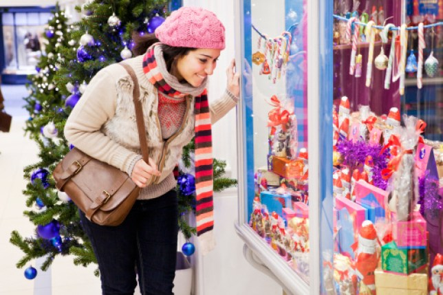 Woman looking in shop window at christmas display.