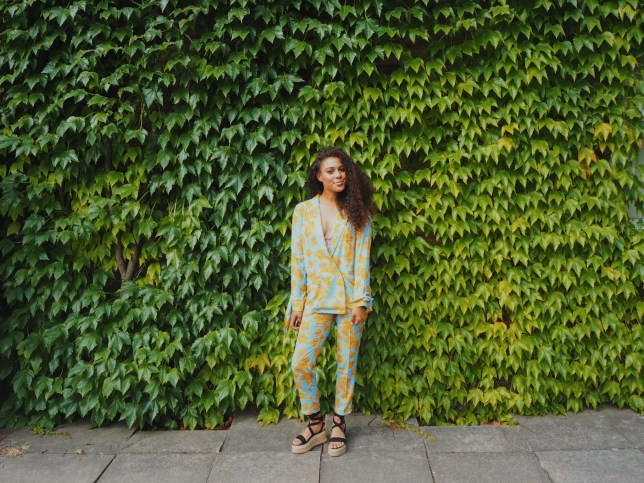 Evie Muir standing in front of a vine wall