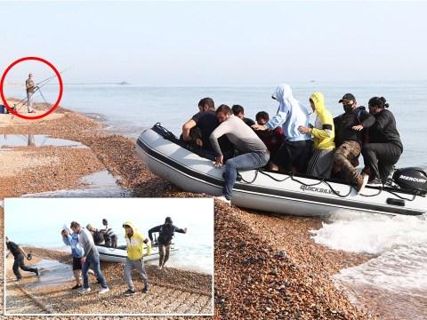 Migrants run past fisherman after landing dinghy on Kent beach