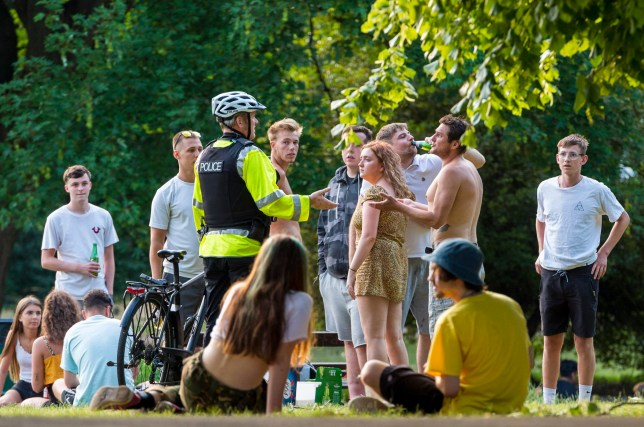 A police officer speaks to groups of more than six young people in St Andrews Park in the evening, after some lockdown restrictions due to the coronavirus covid-19 pandemic have been lifted by the UK