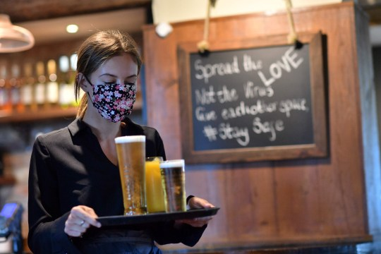 A staff member wears a face mask as she serves customers at the The Shy Horse pub and restaurant in Chessington, Greater London on July 4, 2020, on the first day of a major relaxation of lockdown restrictions during the novel coronavirus COVID-19 pandemic. - Pubs and restaurants reopen as part of a wider government plan to relaunch the hospitality, tourism and culture sectors and help the UK economy recover from more than three tough months of lockdown. (Photo by Ben STANSALL / AFP) (Photo by BEN STANSALL/AFP via Getty Images)