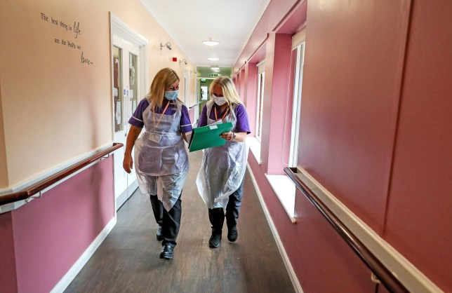 Care workers Jane Ward (left) and Cath Roe on their rounds at Ashwood Court residential care home in Lowton, Warrington, as it reopens to visitors for the first time since lockdown began in March. PA Photo. Picture date: Monday July 20, 2020. Photo credit should read: Peter Byrne/PA Wire