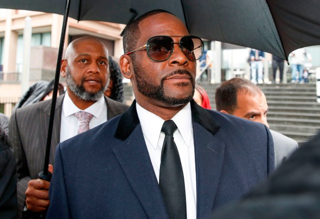 (FILES) In this file photo taken on May 07, 2019, singer R. Kelly leaves the Leighton Criminal Court Building after a hearing on sexual abuse charges, in Chicago, Illinois. - Federal prosecutors on August 12, 2020, announced the arrests of three alleged associates of R. Kelly, saying that they used harassment and threats to try to silence women accusing the disgraced singer of sex crimes. For more than a year the artist born Robert Sylvester Kelly has been awaiting trial in several states for alleged wrongdoings including sex crimes against minors and child pornography. (Photo by KAMIL KRZACZYNSKI / AFP) (Photo by KAMIL KRZACZYNSKI/AFP via Getty Images)
