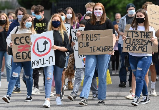Students hold placards as they take part in a protest march from Codsall Community High School to the constituency office of Gavin Williamson, Conservative MP for South Staffordshire and Britain's current Education Secretary, in Codsall near Wolverhampton, central England on August 17, 2020, to demonstrate against the downgrading of A-level results. - The British government faced criticism after education officials downgraded more than a third of pupils' final grades in a system devised after the coronavirus pandemic led to cancelled exams. Although the newly released results for 18-year-olds showed record-high grades and more students accepted to university courses, exam boards downgraded nearly 40 percent of pupils' grades in England. (Photo by Paul ELLIS / AFP) (Photo by PAUL ELLIS/AFP via Getty Images)