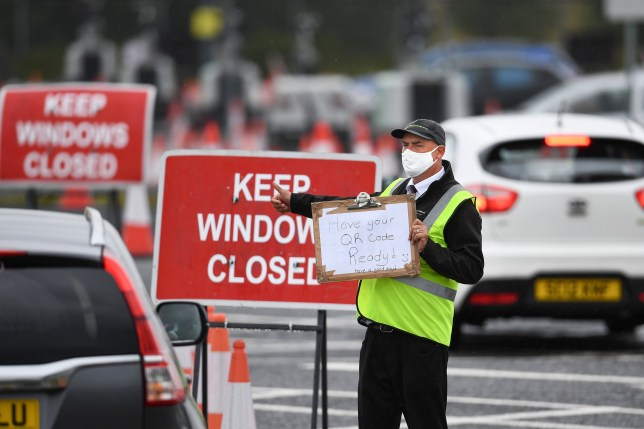 An employee directs members of the public drive into a coronavirus testing centre at Glasgow Airport
