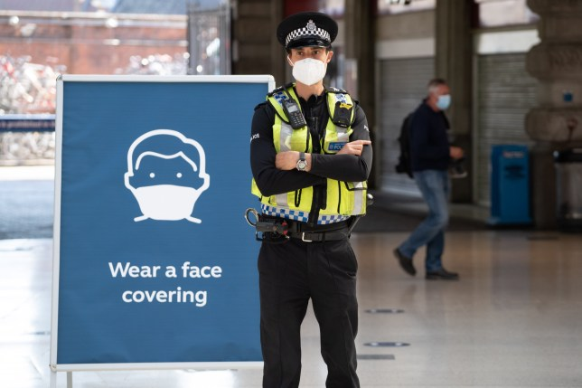 A police officer wears a face mask as he stands on the concourse at Waterloo Station in London on June 15, 2020 after new rules make wearing face coverings on public transport compulsory while the UK further eases its coronavirus lockdown. - New coronavirus pandemic rules coming into force on June 15 make wearing face coverings such as masks or scarves compulsory on public transport, as various stores and outdoor attractions open for the first time in nearly three months. (Photo by Niklas HALLE'N / AFP) (Photo by NIKLAS HALLE'N/AFP via Getty Images)