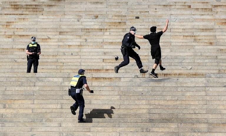La police arrête un manifestant sur les marches du sanctuaire du souvenir.