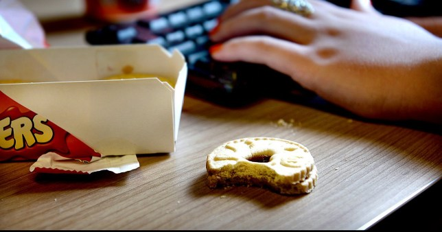 An office workers eats a Jammy Dodger biscuit at their desk, London