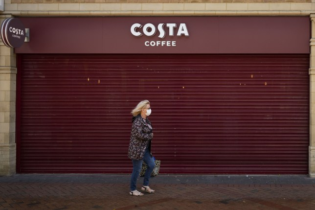 CAERPHILLY, UNITED KINGDOM - MAY 23: A woman walks passed a closed Costa Coffee store while carrying a shopping bag and wearing a surgical face mask during the coronavirus lockdown period on May 23, 2020 in Caerphilly, United Kingdom. The British government has started easing the lockdown it imposed two months ago to curb the spread of Covid-19, abandoning its 'stay at home' slogan in favour of a message to 'be alert', but UK countries have varied in their approaches to relaxing quarantine measures. (Photo by Matthew Horwood/Getty Images) FILE: The County Borough Of Caerphilly, Wales To Be Placed Under A Local Lockdown.