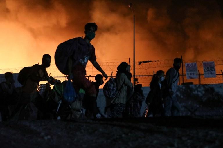 Les réfugiés et les migrants portent leurs affaires alors qu'ils fuient un incendie qui brûle dans le camp de Moria, sur l'île de Lesbos, en Grèce, le 9 septembre 2020.