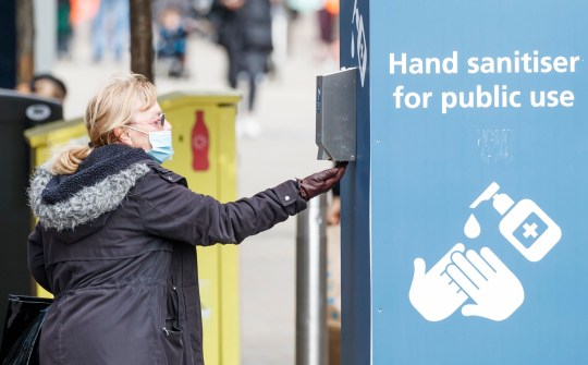 A woman uses a public hand sanitizer in Leeds city center, West Yorkshire, where stricter lockdown measures can be introduced locally after an increase in coronavirus infections.  Photo PA.  Photo date: Friday, September 11, 2020. The head of city council has called for the authority to be granted greater intervention powers to stem the spread of the virus, the latest data from Public Health England showing that just over 500 new cases of Covid-19 were recorded in Leeds in the seven days leading up to September 7.  See the story of PA HEALTH Coronavirus.  Photo credit should read: Danny Lawson / PA Wire