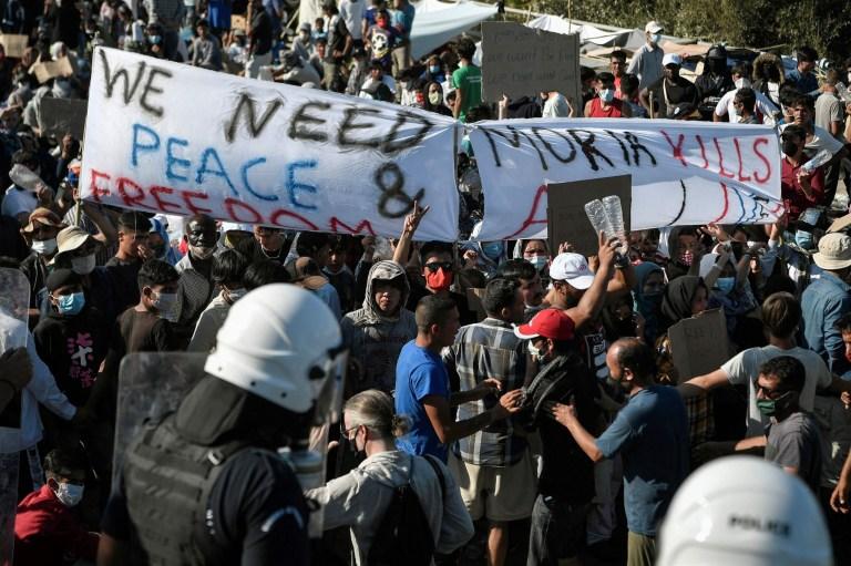 Les réfugiés et les migrants du camp détruit de Moria manifestent pour appeler à leur réinstallation devant un blocus policier près de la ville de Mytilene et du camp de Kara Tepe, le 11 septembre 2020, sur l'île de Lesbos.  Le 10 septembre, les autorités grecques se sont précipitées pour abriter des milliers de demandeurs d'asile sans abri à Lesbos après que le principal camp de migrants de l'île ait été ravagé par des incendies consécutifs, qui ont détruit la partie officielle du camp abritant 4000 personnes.  8.000 autres vivaient dans des tentes et des cabanes de fortune autour du périmètre et beaucoup ont été gravement endommagés.  (Photo par LOUISA GOULIAMAKI / AFP) (Photo par LOUISA GOULIAMAKI / AFP via Getty Images)