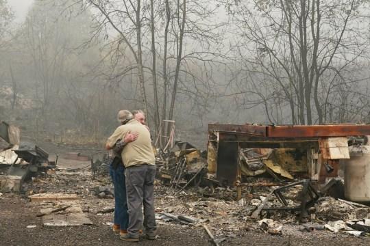 Larry Weyand embrasse Darwin Seim devant la maison mobile incendiée de Weyand au Clackamas River RV Park le 14 septembre 2020 à Estacada, Oregon.