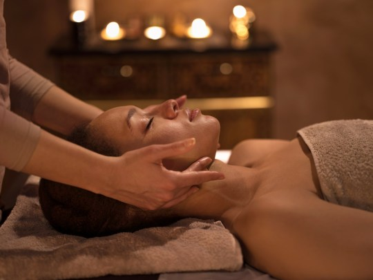 Relaxed African American woman receiving head massage and enjoying at spa with her eyes closed.
