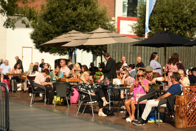 People enjoy a drink in the late summer sunshine in Liverpool city centre, north-west England on September 18, 2020 after the British government imposed fresh restrictions on the city after an rise in cases of the novel coronavirus. - Millions more people in northern and central England faced new restrictions over a surge in coronavirus cases, the British government announced on Friday, as it warned another national lockdown could be imminent. Tighter regulations preventing people from socialising with anyone outside their household will come into force from next Tuesday across parts of the northwest, the Midlands and West Yorkshire. Food and drink venues in the northwestern areas of Merseyside, Warrington, Halton and Lancashire will be restricted to table service only, while pubs and bars will have to shut early by 10:00 pm (2100 GMT). (Photo by Oli SCARFF / AFP) (Photo by OLI SCARFF/AFP via Getty Images)
