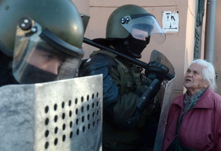 Une femme âgée s'entretient avec des policiers biélorusses lors d'un rassemblement pour protester contre les résultats de l'élection présidentielle à Minsk, en Biélorussie, le 20 septembre 2020.