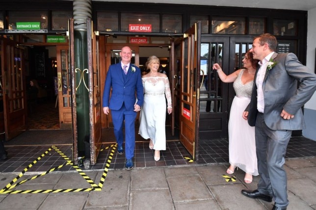 ROCHDALE, ENGLAND - JULY 04: Newly weds Stuart and Diana Greenwood celebrate their wedding day at the Regal Moon JD Wetherspoons pub on July 04, 2020 in Rochdale, England. The UK Government announced that Pubs, Hotels and Restaurants can open from Saturday, July 4th providing they follow guidelines on social distancing and sanitising. (Photo by Anthony Devlin/Getty Images)