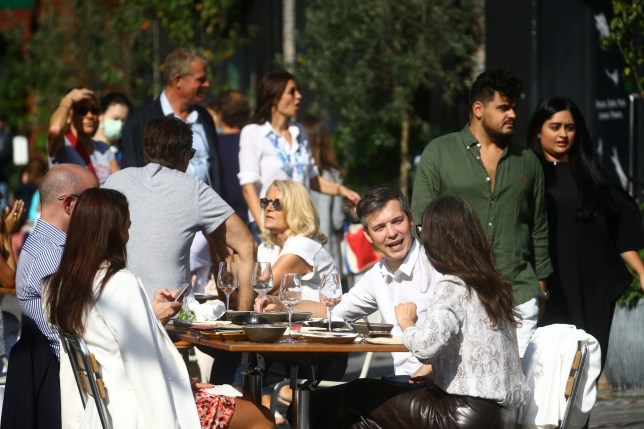 People talk in an outdoor seating at a restaurant, amid the spread of the coronavirus disease (COVID-19) in Chelsea, London, Britain September 22, 2020.