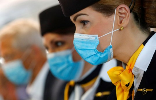 Employees of German airline Lufthansa wear protective masks as they wait for passengers at a boarding gate during a guided tour hosted by Fraport airport and the airline to present their hygiene procedures as travel bans are lifted after the coronavirus disease (COVID-19) outbreak at the airport in Frankfurt, Germany, June 17, 2020