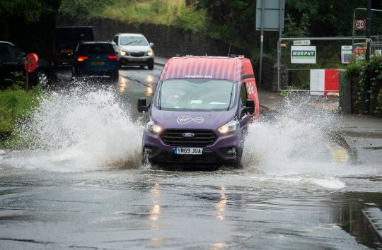 Traffic drives through a flooded road