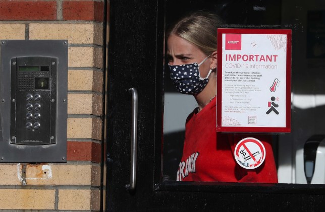 A student leaves one of the accommodation blocks at Murano Street Student Village in Glasgow, where Glasgow University students are being tested at a pop up test centre. A range of new measures to combat the rise in coronavirus cases come into force in Scotland on Friday, including a ban on indoor household visits and a curfew for pubs and restaurants. PA Photo. Picture date: Friday September 25, 2020. See PA story SCOTLAND Coronavirus. Photo credit should read: Andrew Milligan/PA Wire