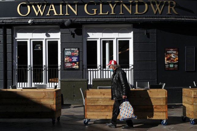 A man wearing a protective face mask walks past the Owain Glyndwr pub in Cardiff, south Wales on September 27, 2020, during preparations for the reinstatement of a lock-down, ahead of a 6pm deadline, as new restrictions are introduced to combat the spread of the coronavirus covid-19. - Cardiff will become the first UK capital to go into local lockdown since a national shutdown earlier this year. The new restrictions in Wales, which bar people from entering or leaving areas unless for work, education or another valid reason, will also apply in second city Swansea, from 6pm (1700 GMT) Sunday, and in the town of Llanelli from Saturday. (Photo by Geoff Caddick / AFP) (Photo by GEOFF CADDICK/AFP via Getty Images)