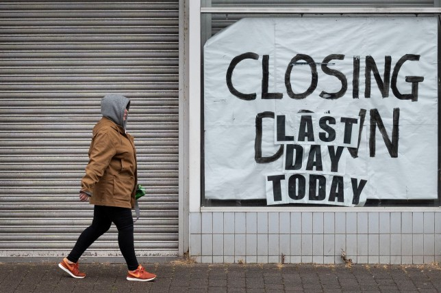 A woman walks passed a closed-down shop on June 10, 2020 in Aberdare, UK, in the middle of coronavirus lockdown