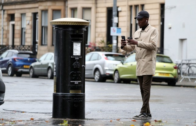 A Member of the public takes a photograph of a black postbox to mark Black History Month
