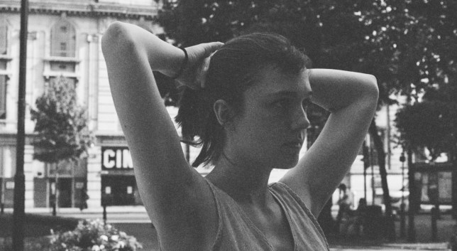 Black and white image of August Lamm putting her hair up