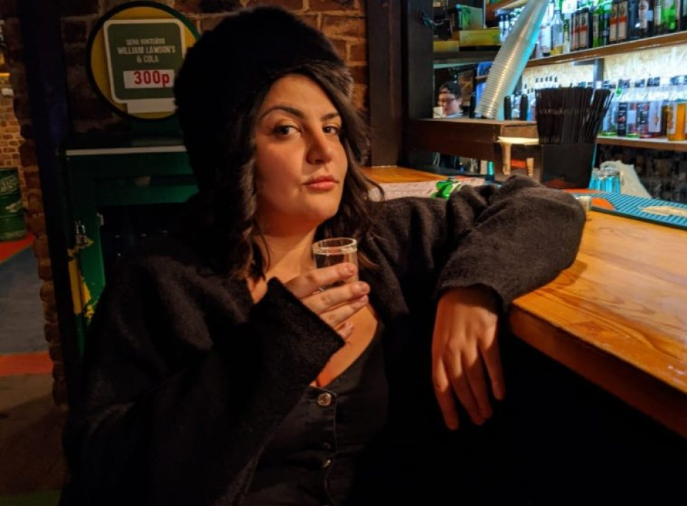 Almara Abgarian holding a shot of vodka in a bar in Russia.