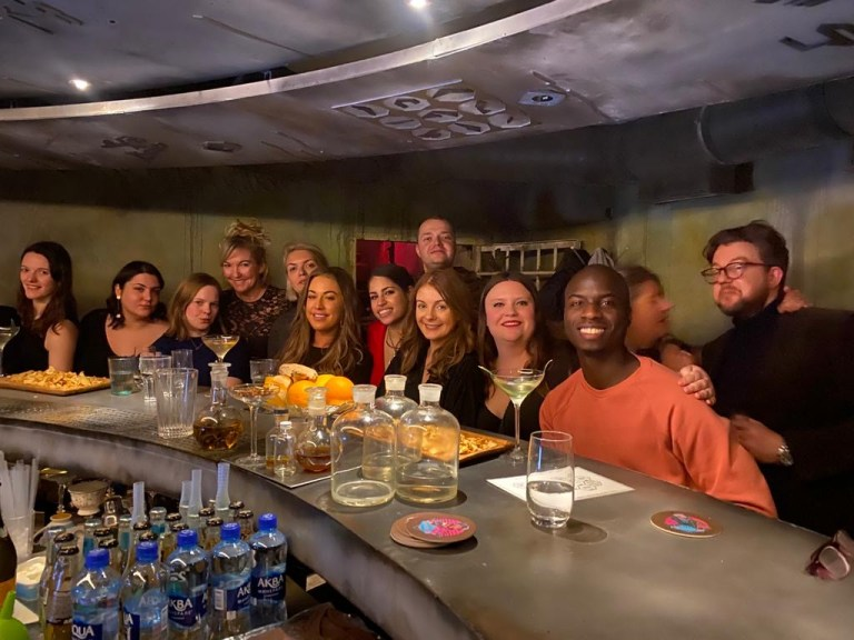 A group of people at a bar in Russia, posing together.