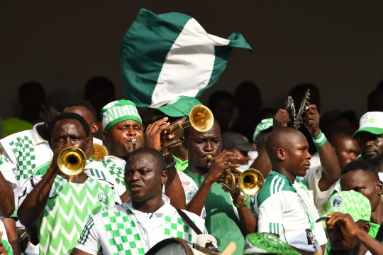 People playing instruments and wearing the Nigerian flag colours.