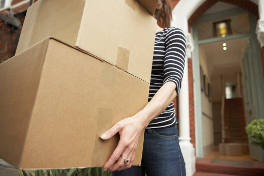 A woman carrying moving boxes.