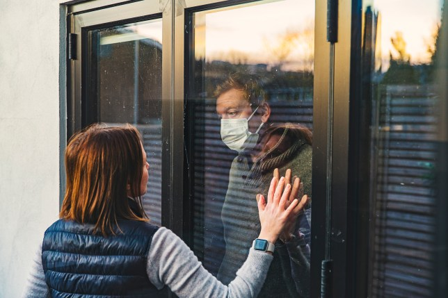Man inside puts his hand to the window as a woman outside places her hand against it