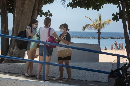 Women wearing masks arrive at Las Teresitas beach in the Spanish Canary Island of Tenerife.