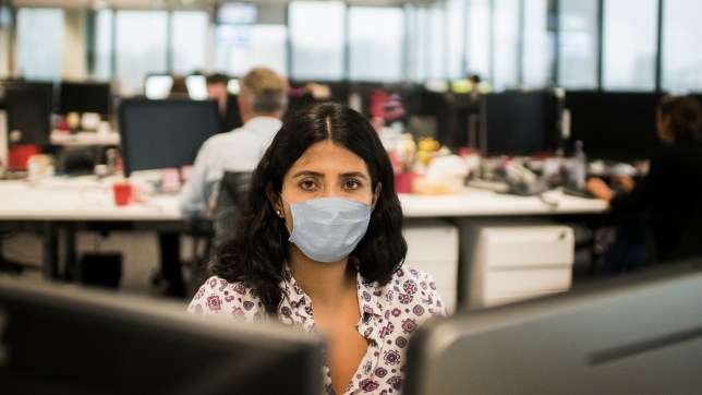 Woman wearing face mask in an office.