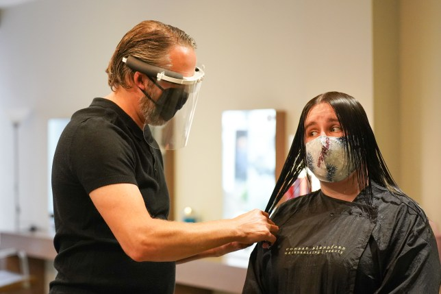 Hairdresser wearing a face mask cuts the hair of a lady who is wearing a face mask too.
