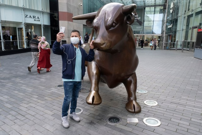 Man wearing  a face mask stands next to a statue of a bull at the Bullring in Birmingham