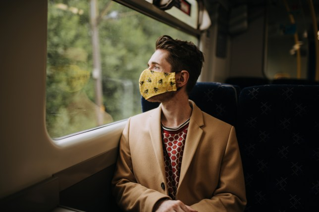 Train commuter wearing PPE face mask for safety.