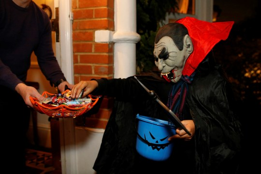 A child dressed as a Vampire goes Trick or Treating.