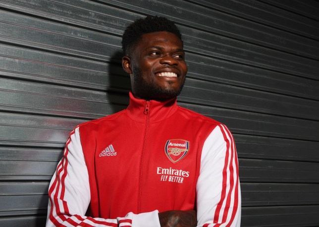 Thomas Partey poses in Arsenal's gear after his transfer move from Atletico Madrid