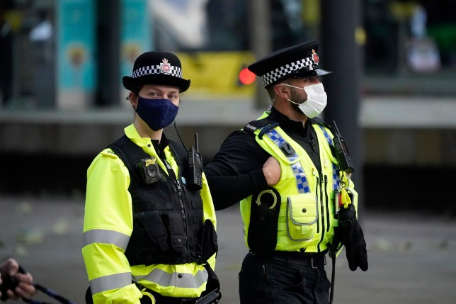 Police officers wear face masks as they patrol.