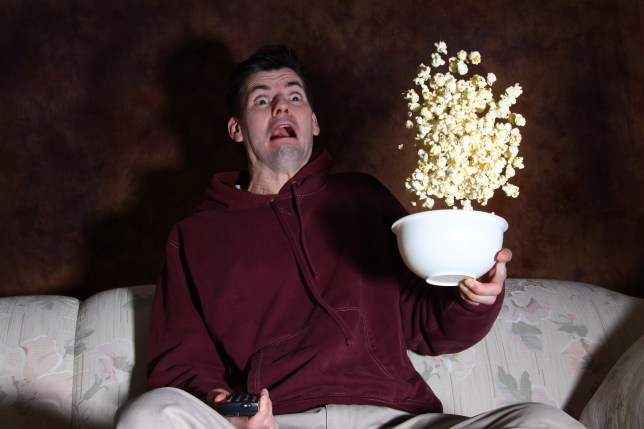 Man loses his popcorn because he gets startled with fright.