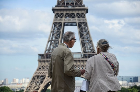 an old couple in front of the eiffel tower