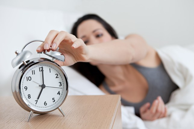 Woman reaching for her alarm clock.