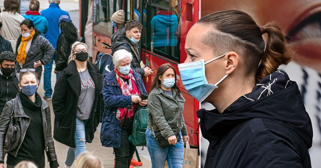 Composition showing Londoners in masks outside a red bus