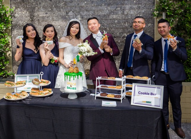 Couple holding up subs on their wedding day surrounded by their guests