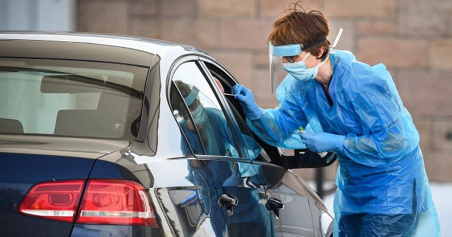 Staff in PPE conducts a drive thru coronavirus test.